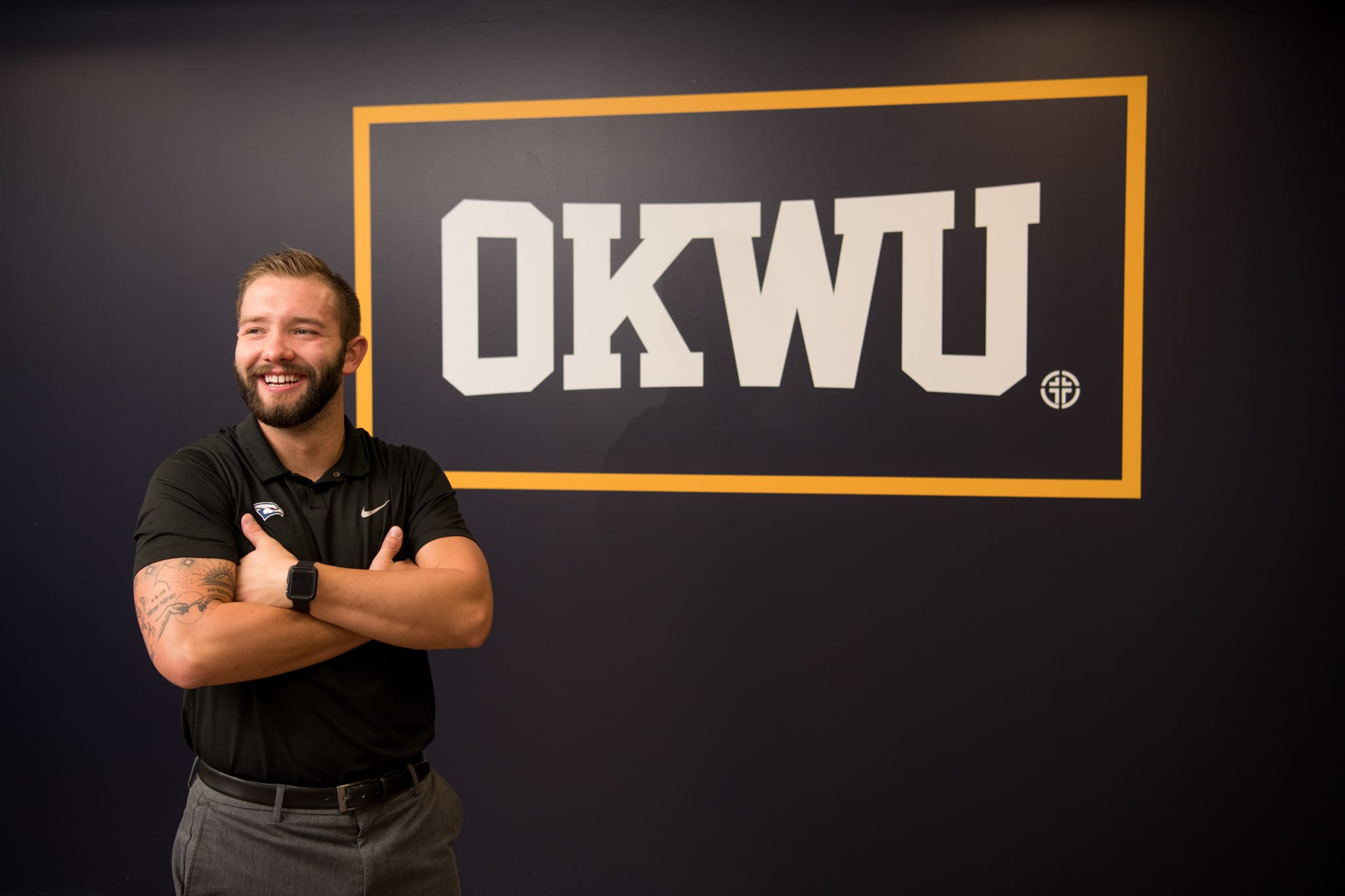 Jake Feickert standing next to the large OKWU mural