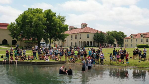 Students being baptized in pond